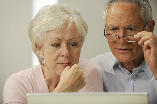 Photo of Older Man & Women Looking at a Computer