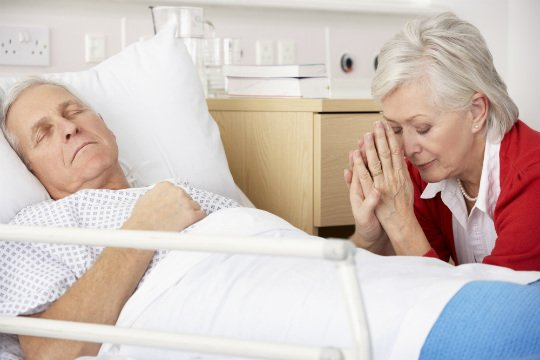 Photo of woman praying bedside for Husband